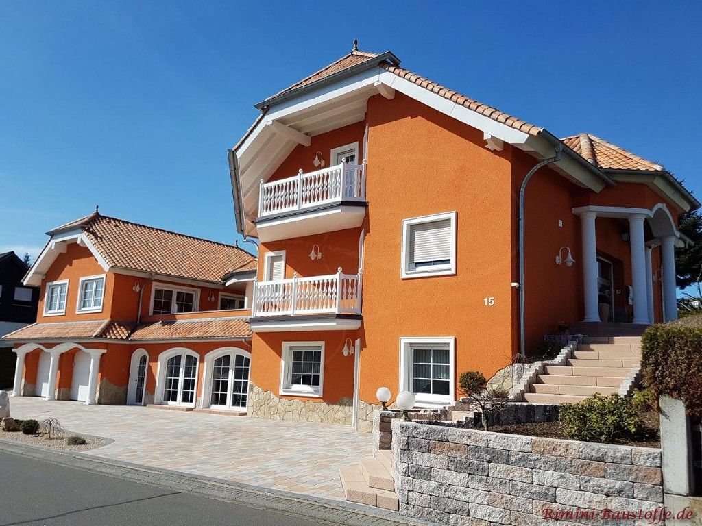 Eine kraeftige orangefarbene Putzfassade wirkt sehr mediterran