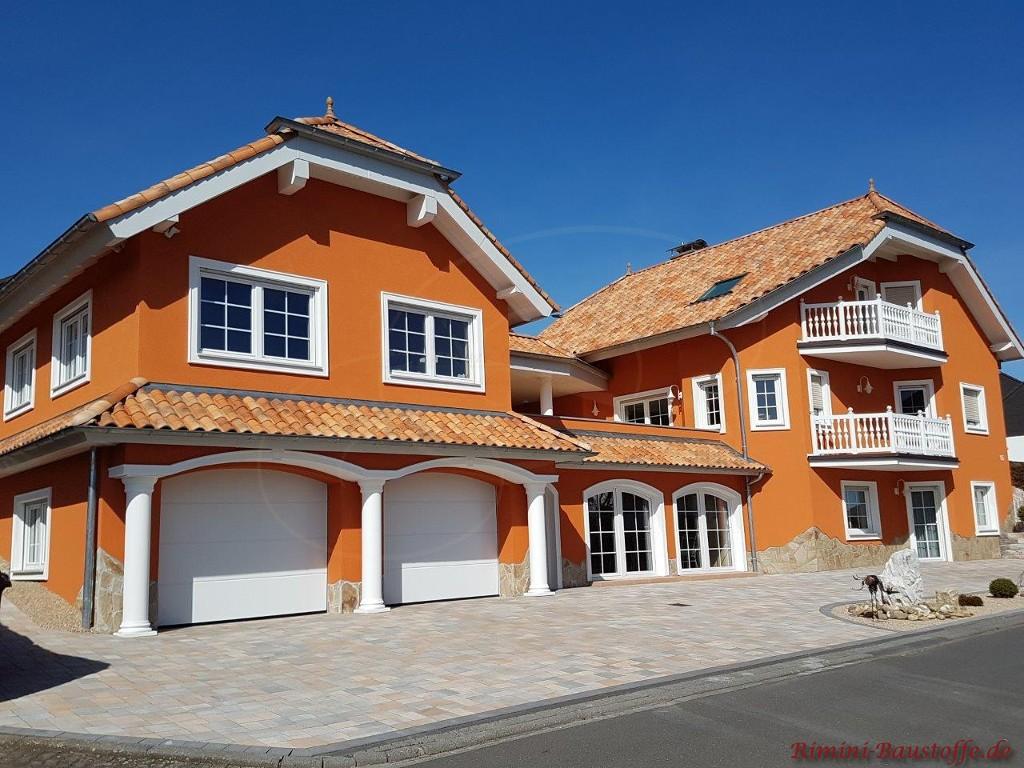 schoene Farbkombination einer kraeftigen orangen Fassade und weissen Fenstern