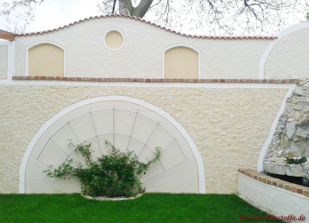 geschwungene Gartenmauer mit Halbschalen eingedeckt