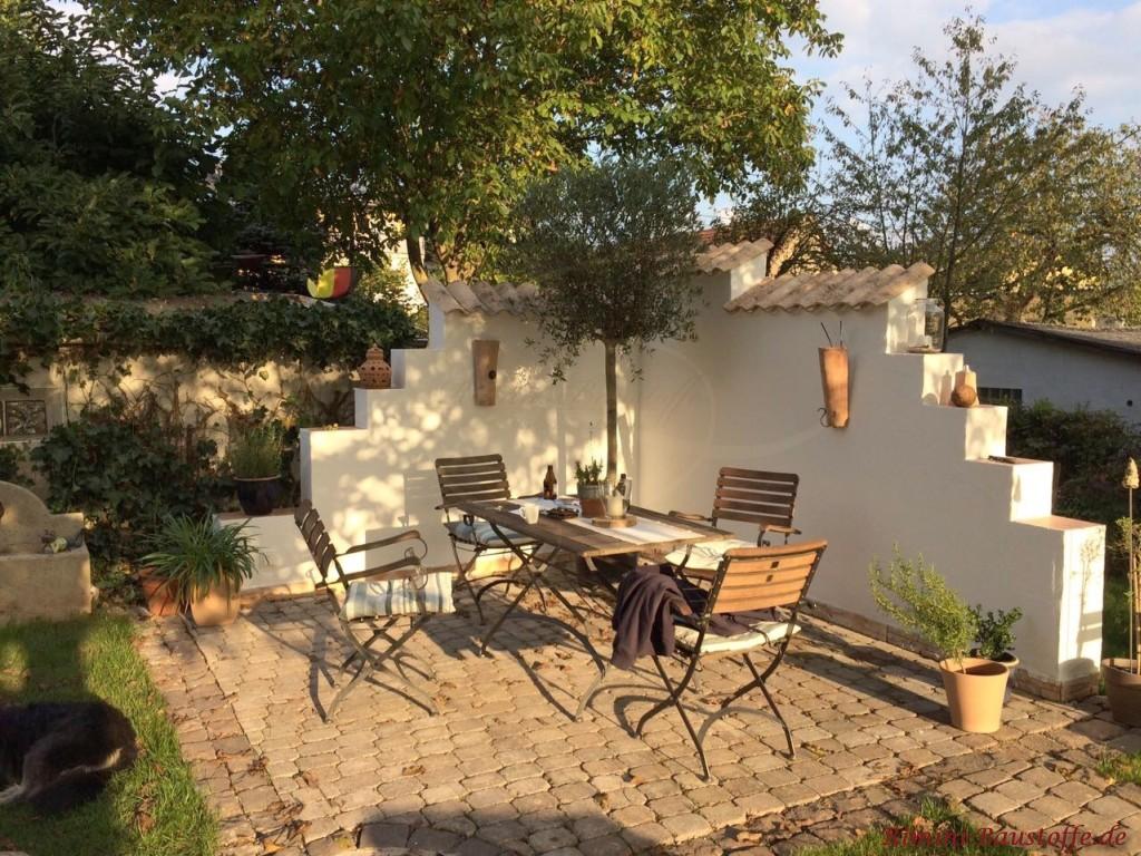 gemuetlich gestaltete Gartenmauer mit mediterranen Elementen