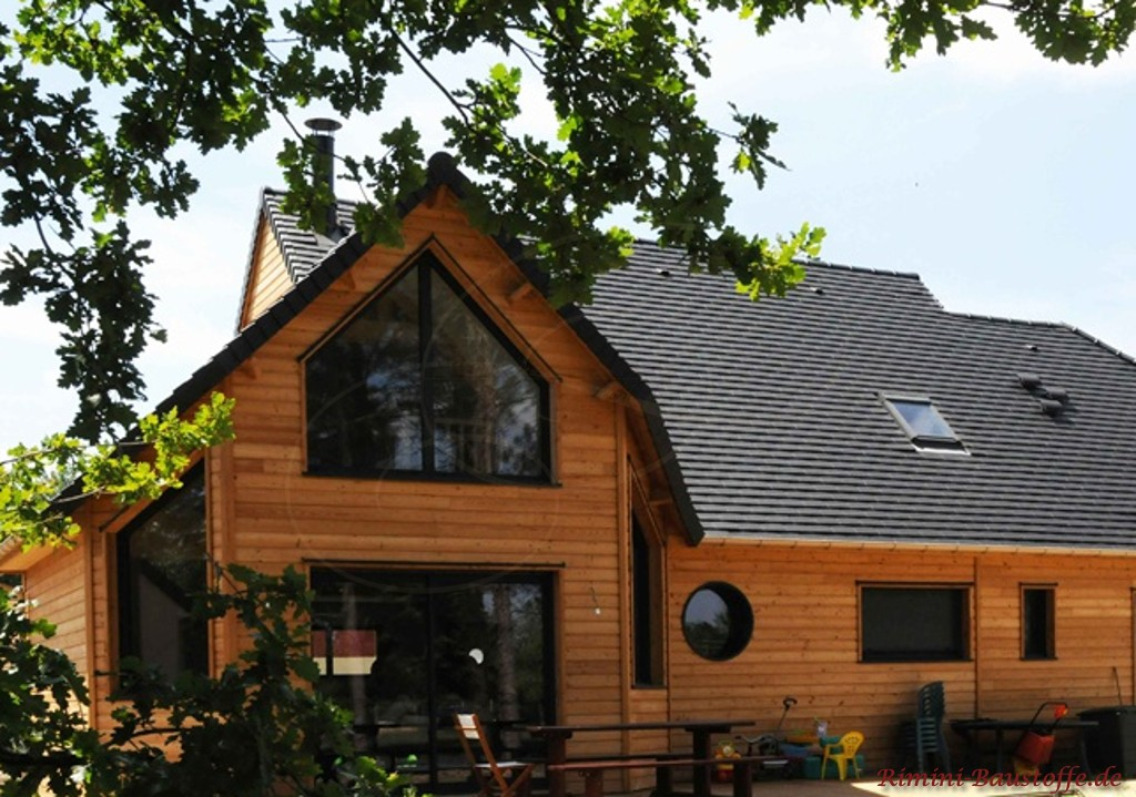 Holzfassade und ein dazu passender anthrazitfarbener Glattziegel