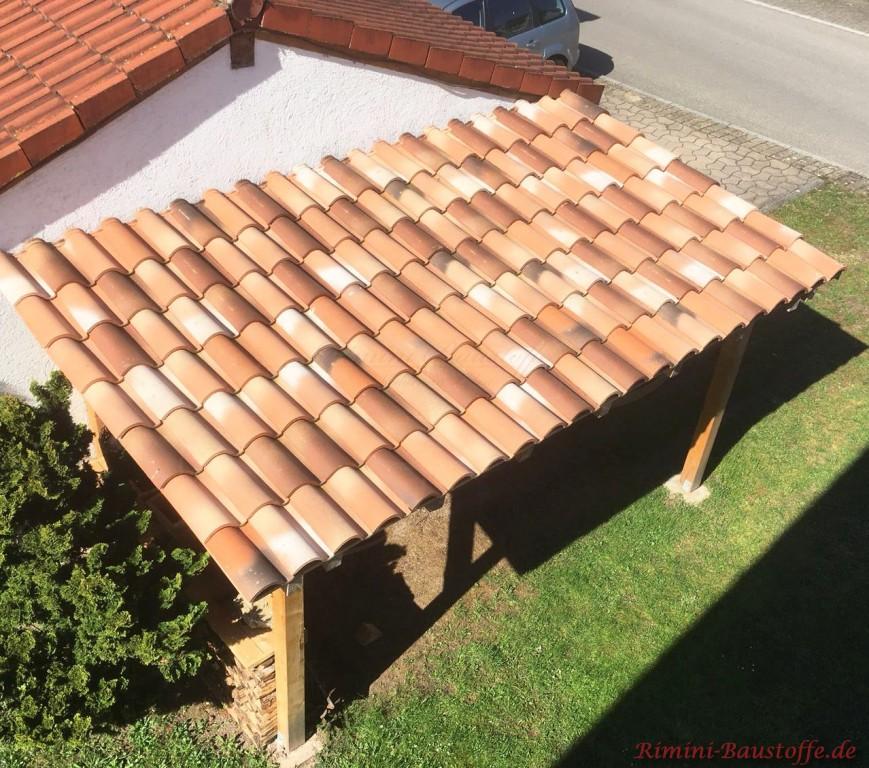 Kleiner Unterstand fuer Holz mediterran eingedeckt