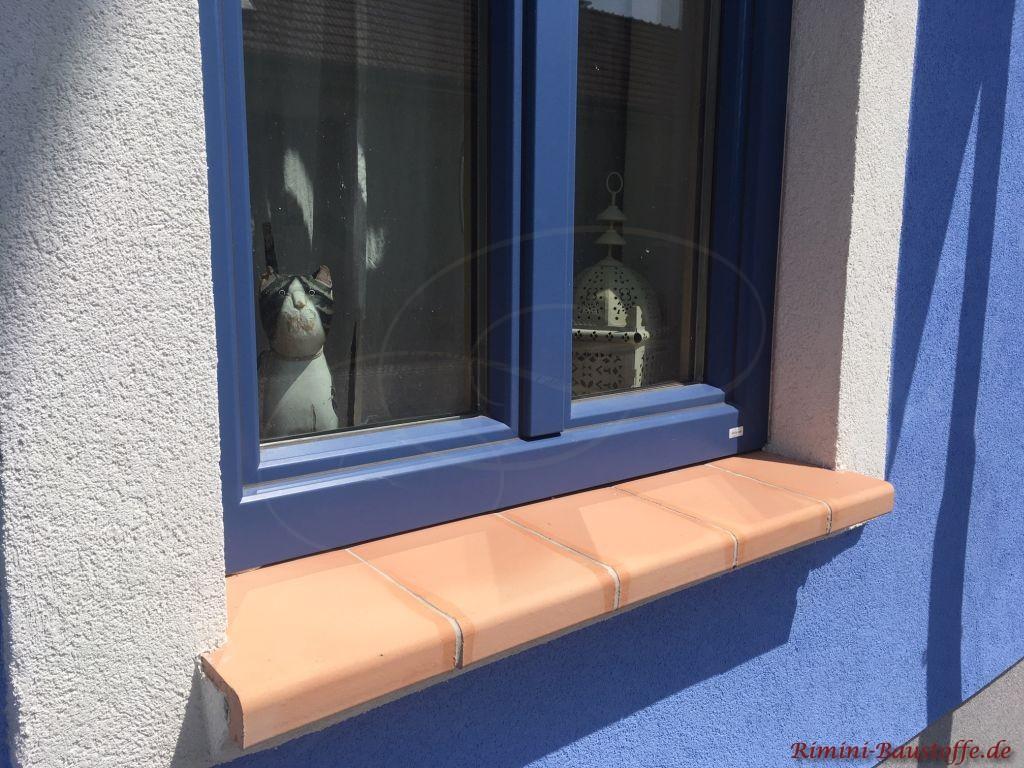 Terracottafarbene Aussenfensterbänke zu einer blauen Putzfassade