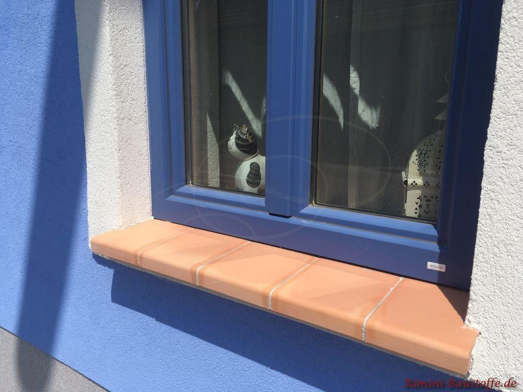 blaue Fenster und blaue Fassade mit einer terracottafarbenen Fensterbank