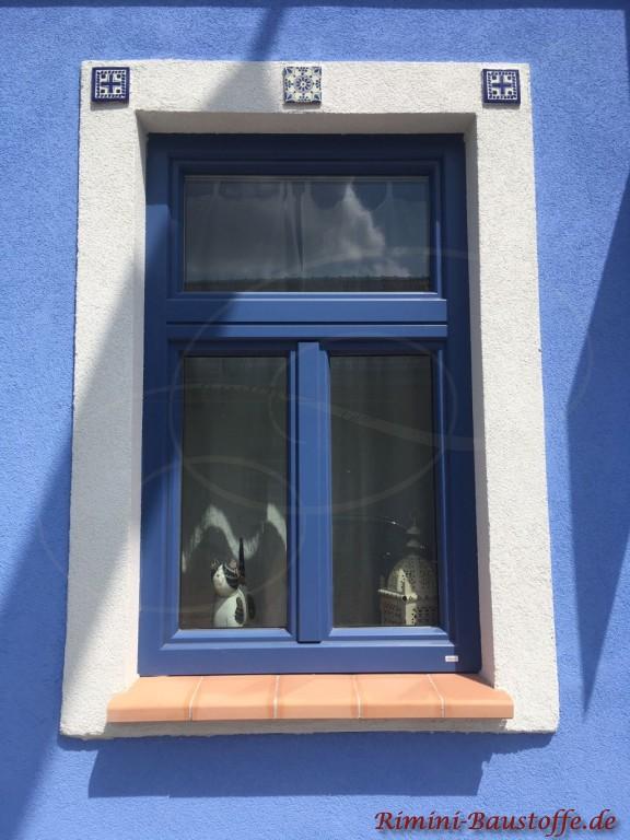 terracottafarbene Tonfensterbank zu einer blauen Fassade und blauen Fenstern