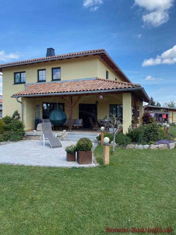 suedlaendisch gestaltetes Wohnhaus mit gelber Putzfassade