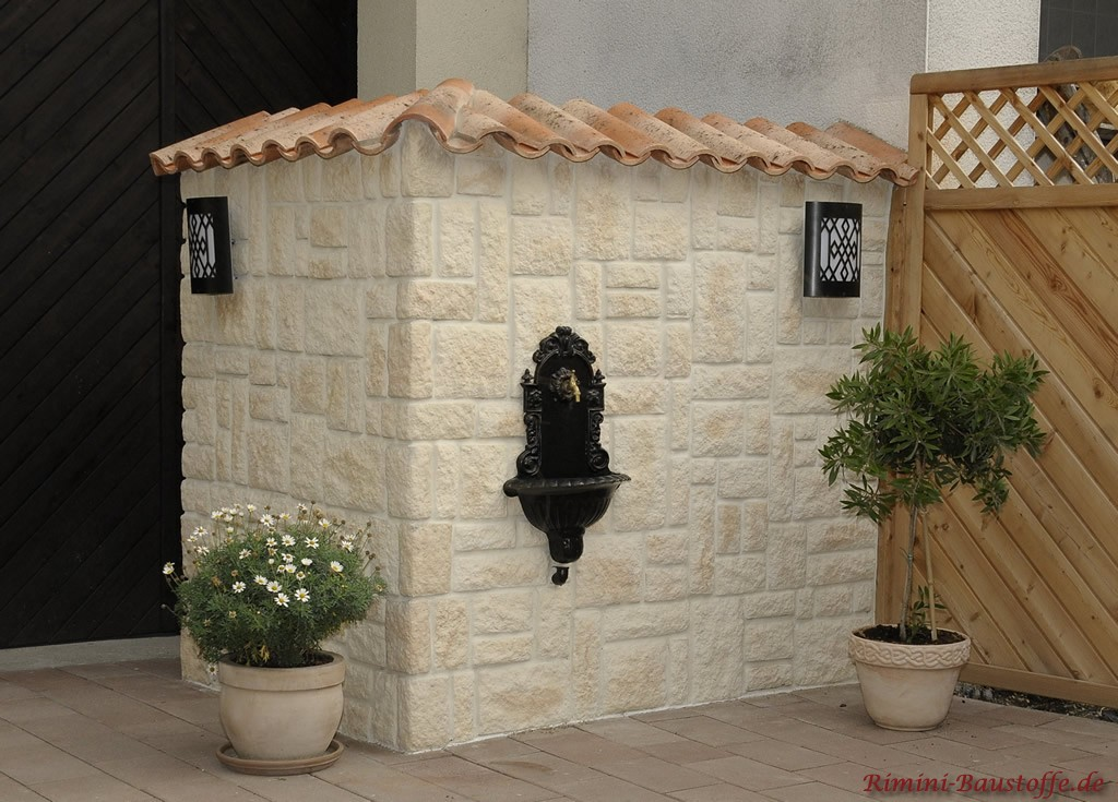 Minimauerstück mit Riemchen verkleidet und spanische Ziegel als Abdeckung. Davor ist ein schwarzer Brunnen zu sehen