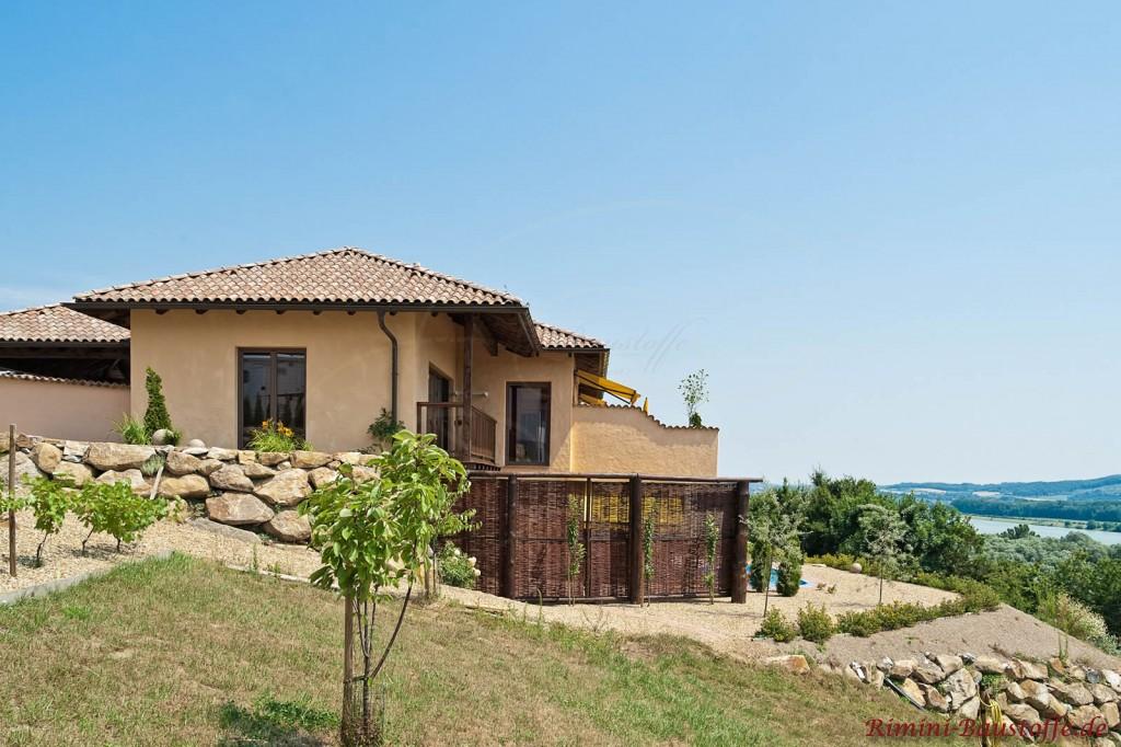 Einfamilienhaus im mediterranem Stil mit Hanglange. Die Fassade ist schön verputzt und die Dachziegel wirken antik