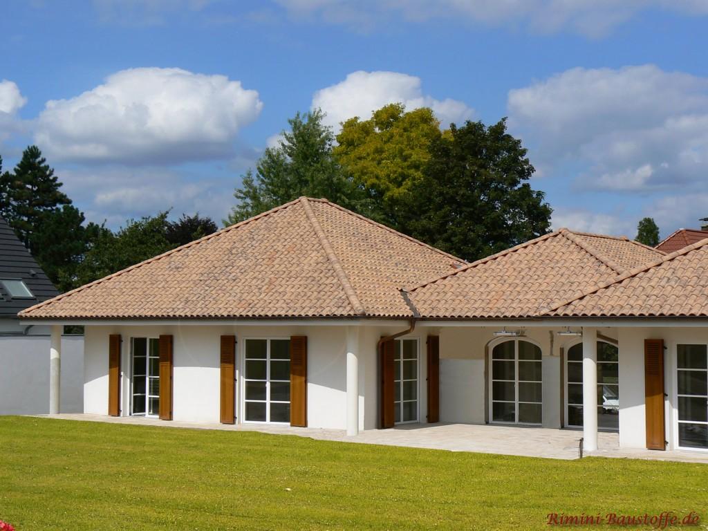 Breiter Bungalow mit weisser Fassade sowie braunen Holzfensterläden und Ziegeln im mediterranen Baustil