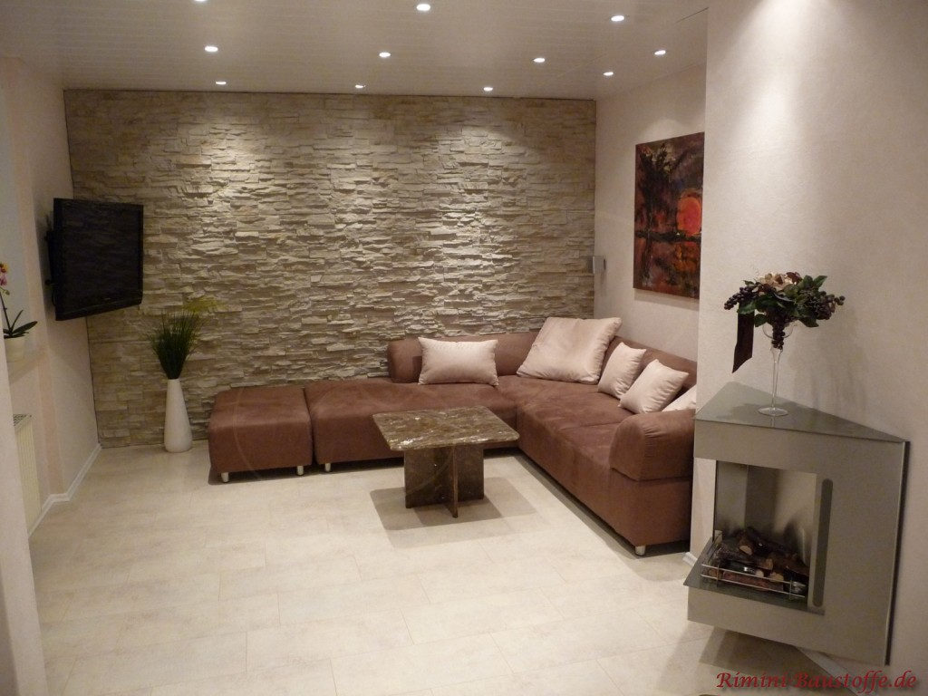 Wohnzimmer mit braunen Möbeln und heller Wohnzimmerwand in Steinoptik