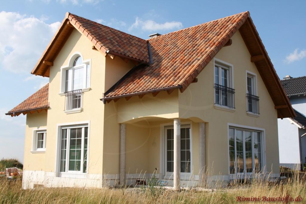 kleines lichtdurchflutetes Wohnhaus mit weißen Sprossenfenstern und einer sehr schönen kräftigen Dachfarbe