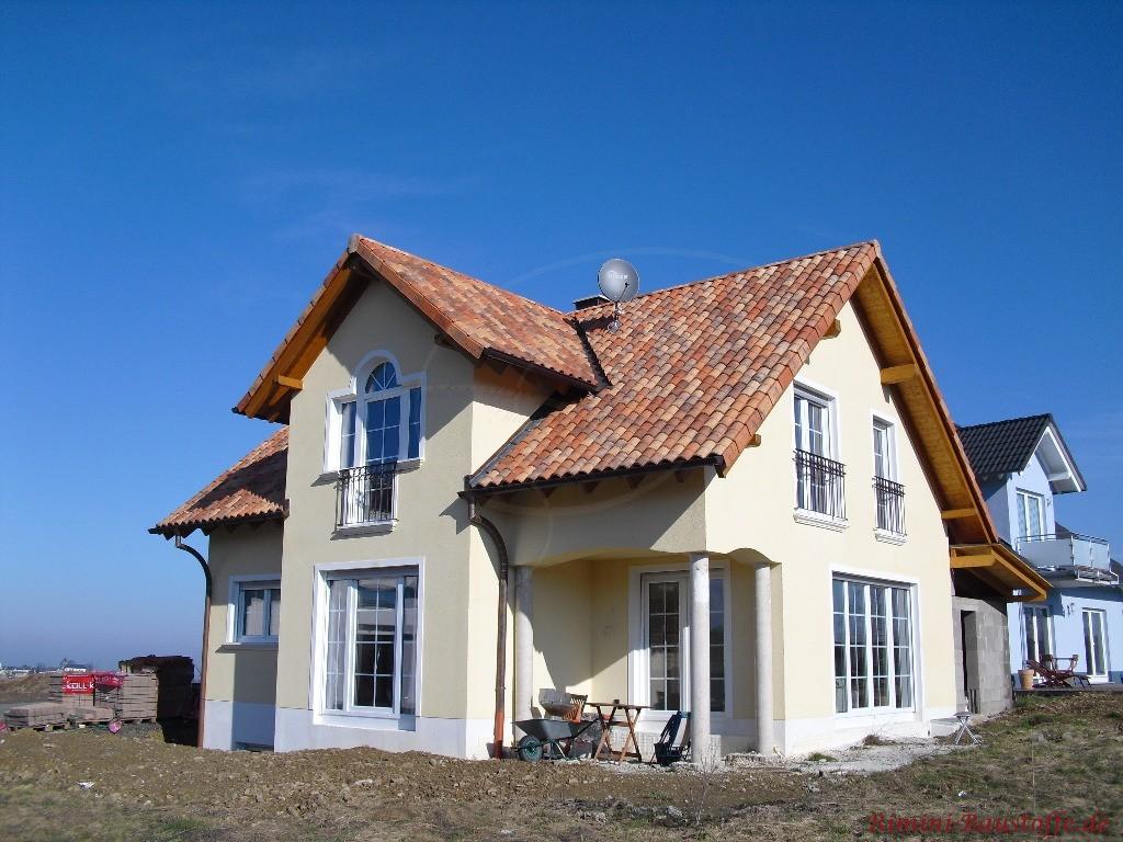schönes Einfamilienhaus mit heller Putzfassade, weißen Fenstern und einer sehr schönen kräftigen mediterranen Dachfarbe