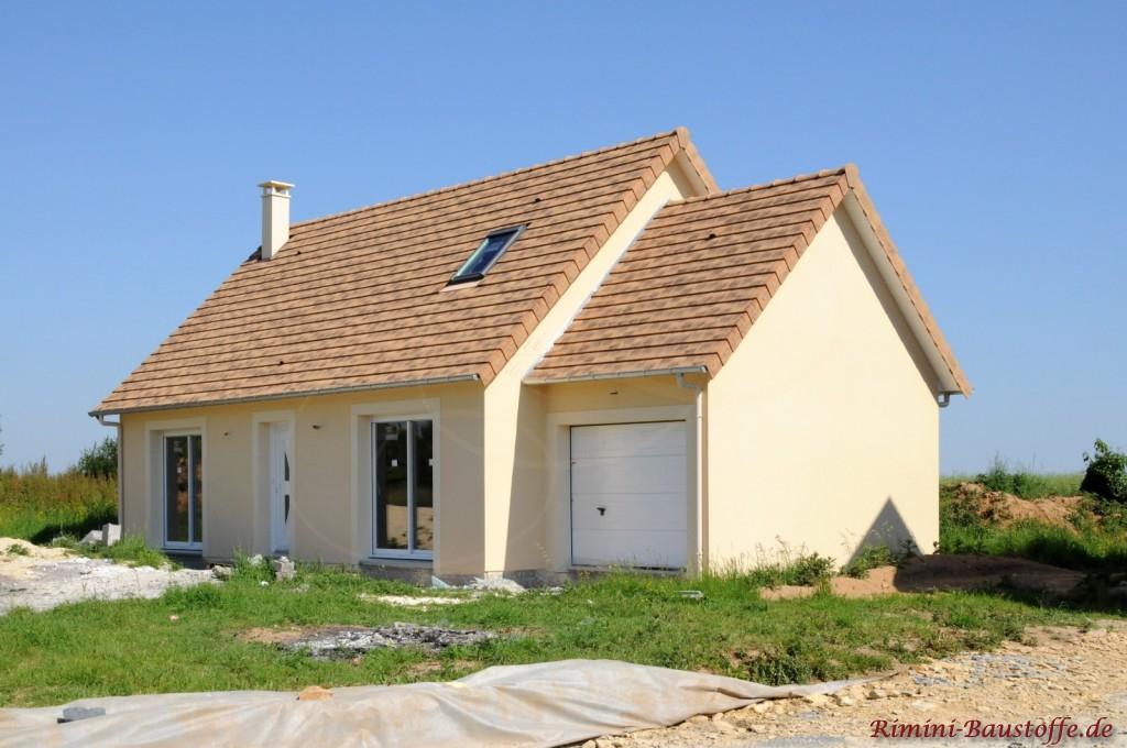 Süsses Haus in gelblichen Farben mit steilem Satteldach und kleiner Garage an der rechten Seite