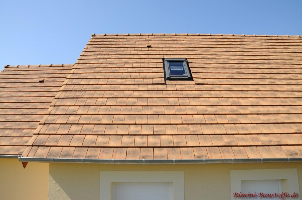 Sandfarbener Tondachziegel im kleinem Format. Die Fassade ist in beige gehalten. Zudem kann man ein kleines Dachfenster sehen