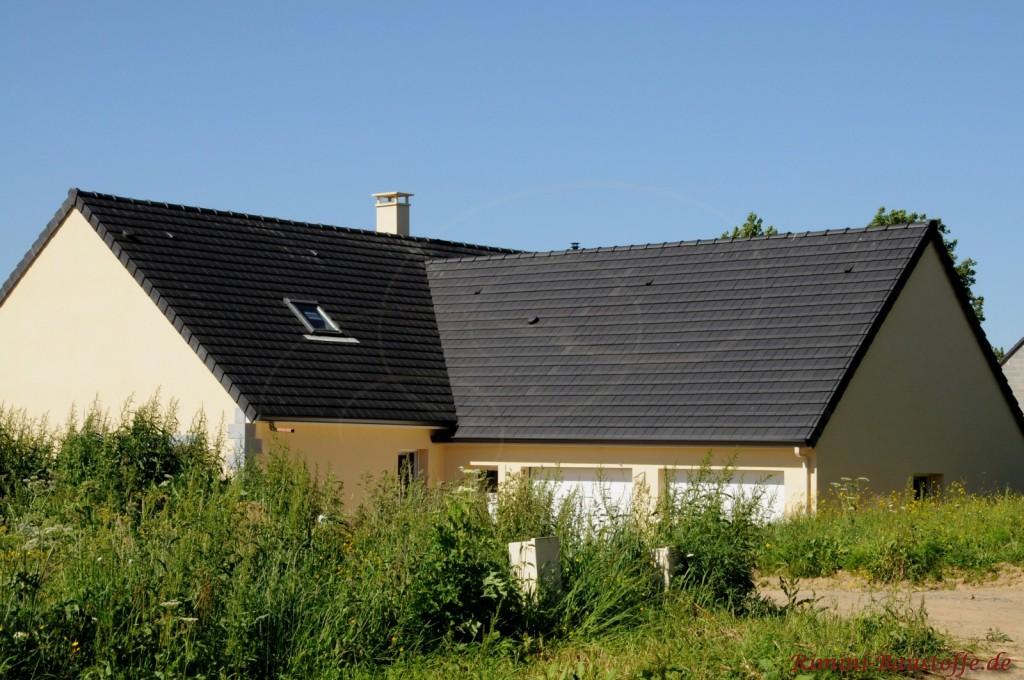 Einfamilienhaus in Frankreich. Der Putz ist in gelblichem Farbton und das Dach ist schwarz Nuanciert.