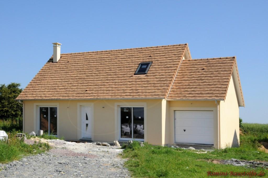 Kleines Einfamilienhaus mit gelben Putz und sandfarbenen Dachziegeln im kleinem Format. Rechts befindet sich eine Garage