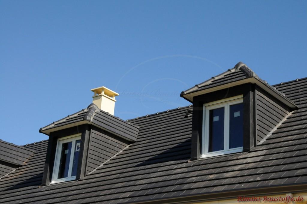 Schöner blauer Himmel und ein pechschwarzes Dach mit zwei Gauben. Das Dach wurde mit dunklen Tondachziegel eingedeckt die gut im Kontrast zu dem