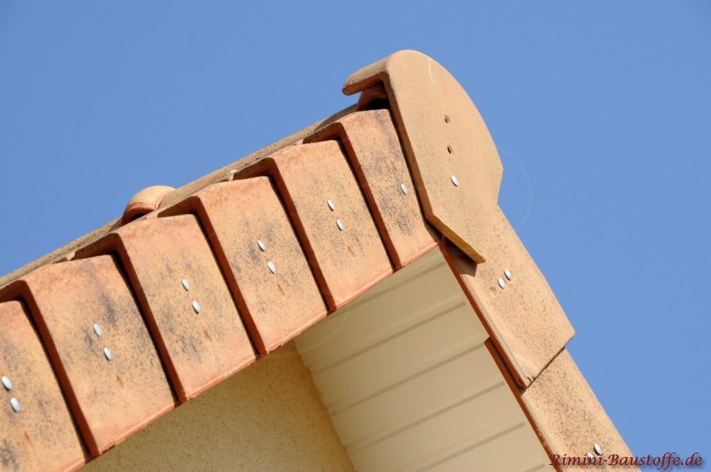 Überstand bei einem Giebeldach das mit beigen Dachziegeln abgedeckt ist.