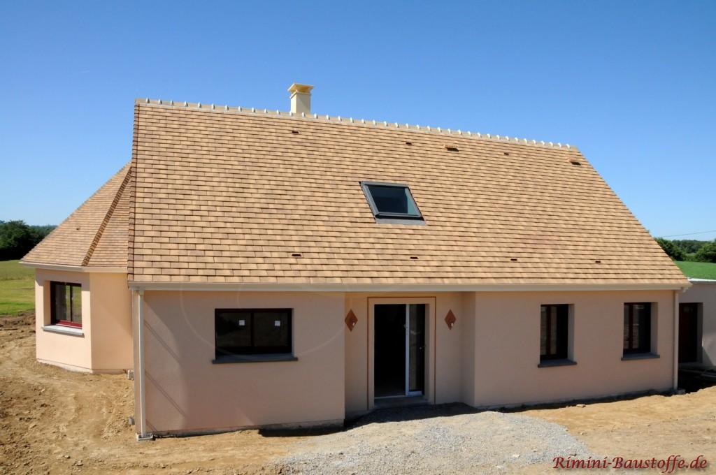 Neubau im südländischen Stil mit heller Putzfassade und beigem Satteldach