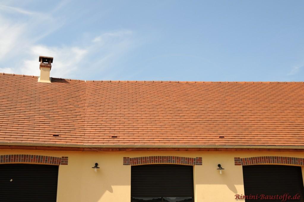 große Satteldachfläche zur gelben Putzfassade und Faschen aus Klinker