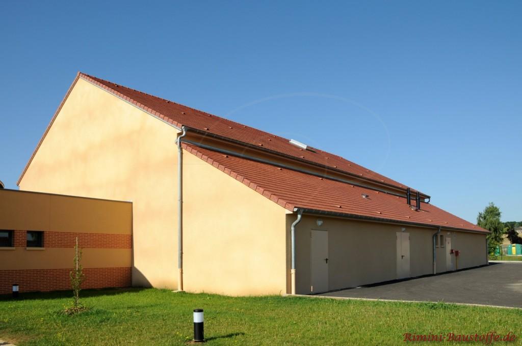 kräftige gelbe Putzfassade mit Changierung un ein kräftiges rotes Satteldach