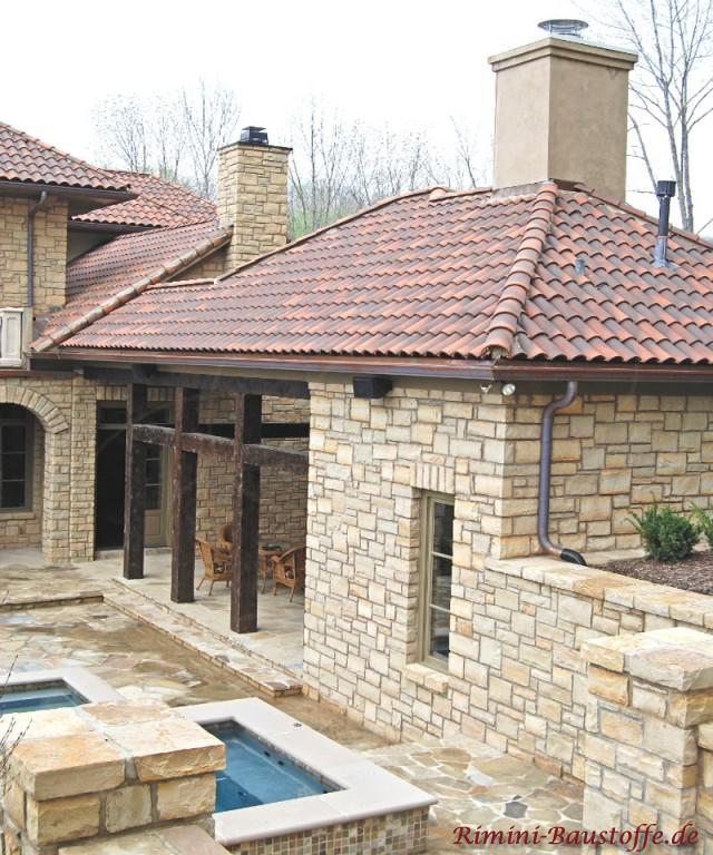 großes Haus mit Natursteinfassade und dunkeln Holzbalken