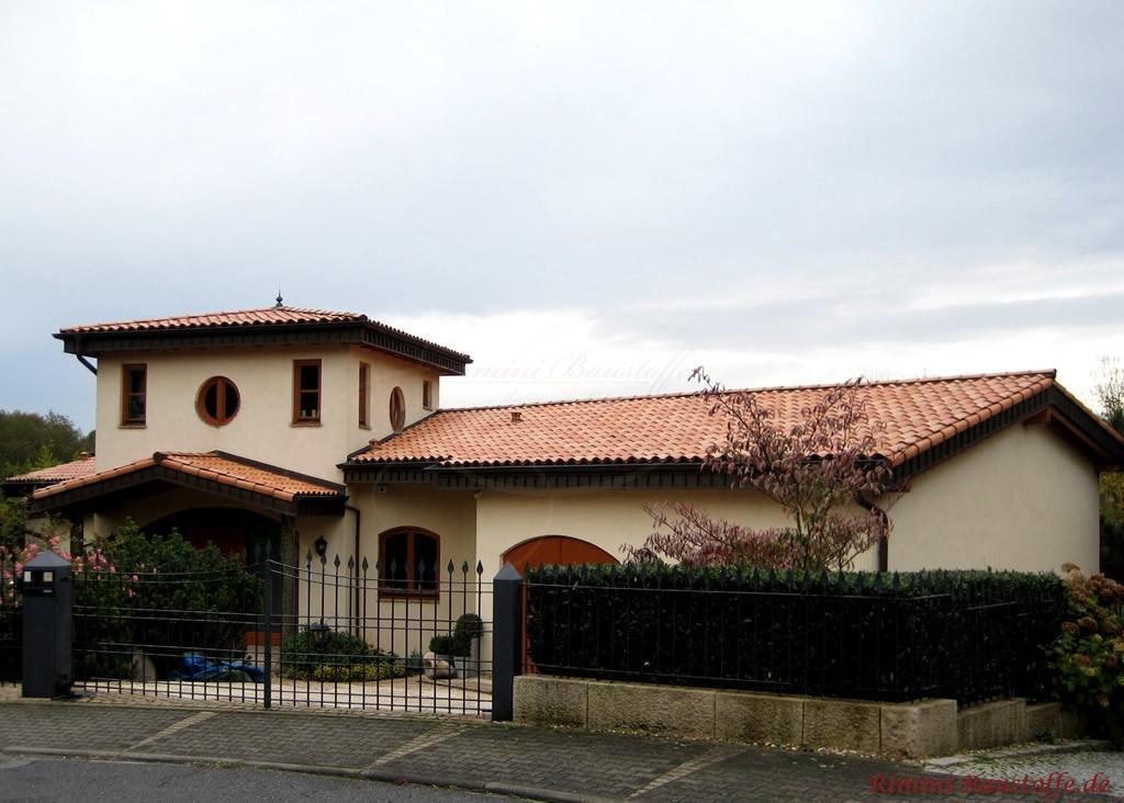 mediterranes Haus mit hellgelber Putzfassade und tradtioneller Halbschaleneindeckung auf dem Dach
