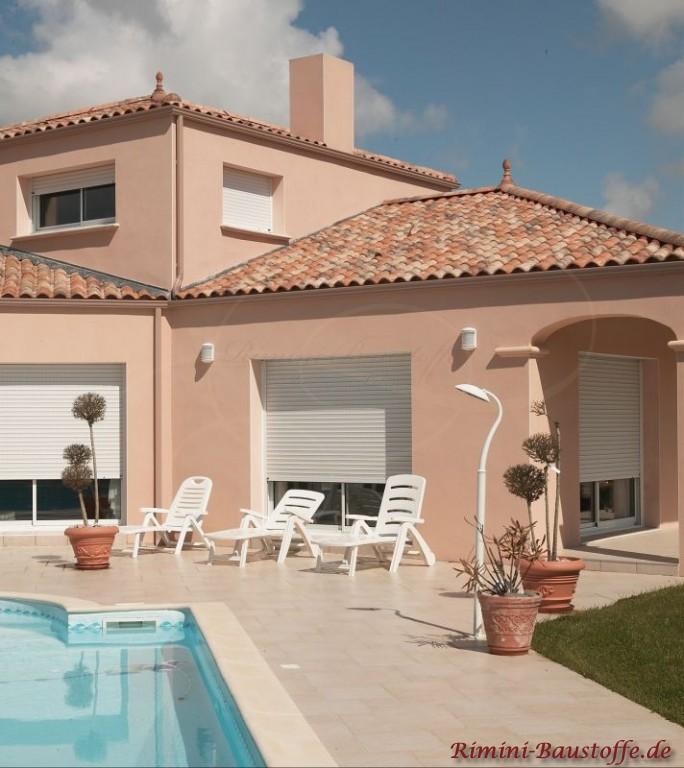 Terrasse in Frankreich. Haus mit rosefarbener Fassade und bunten Dachziegeln