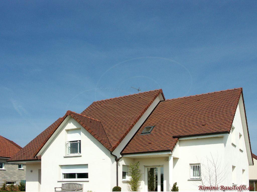 schöne dunkelrote Schindeln auf einem Satteldach pasend zur weissen Putzfassade