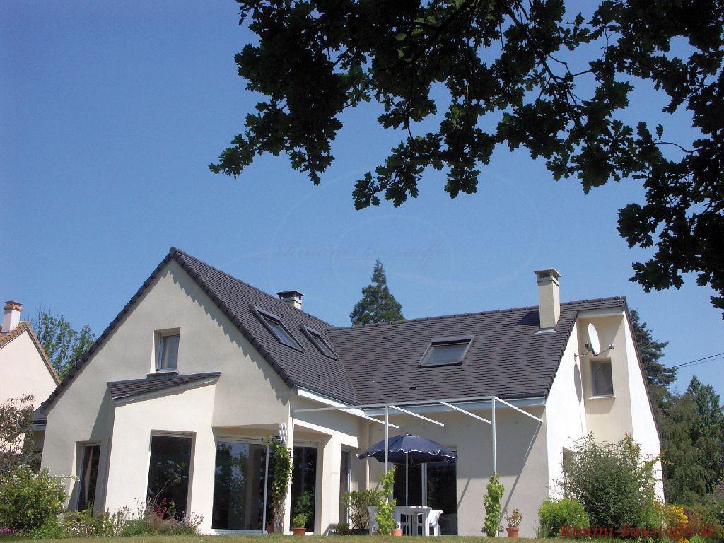 schönes modernes Einfamilienhaus mit weisser Putzfassade und antrazithfarbenen Schindeln