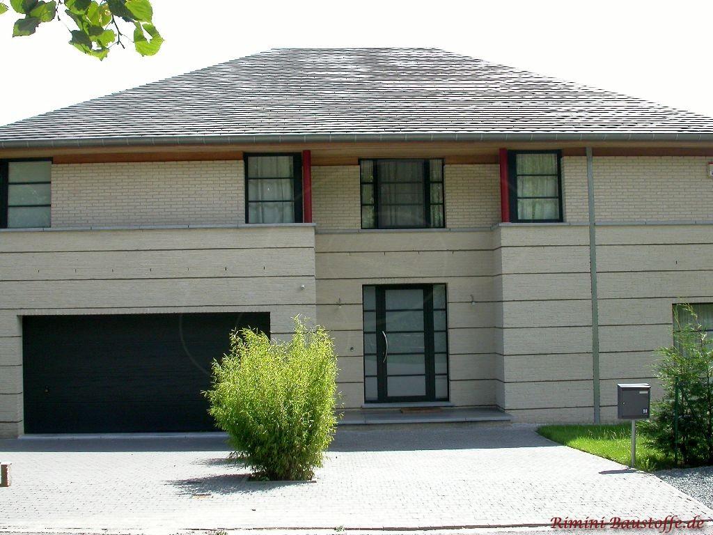 große moderne Villa mit hellem Klinker und antrazithfarbenem Dach