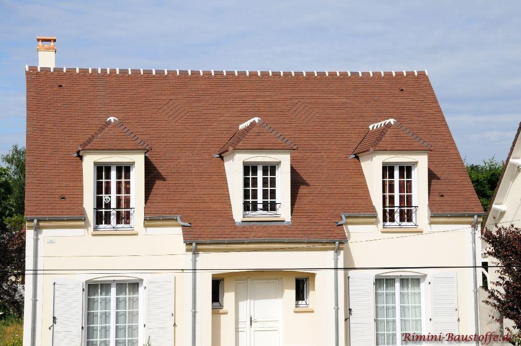 kleines Haus was einer Villa ähnelt mit weisser Putzfassade und rotem Satteldach