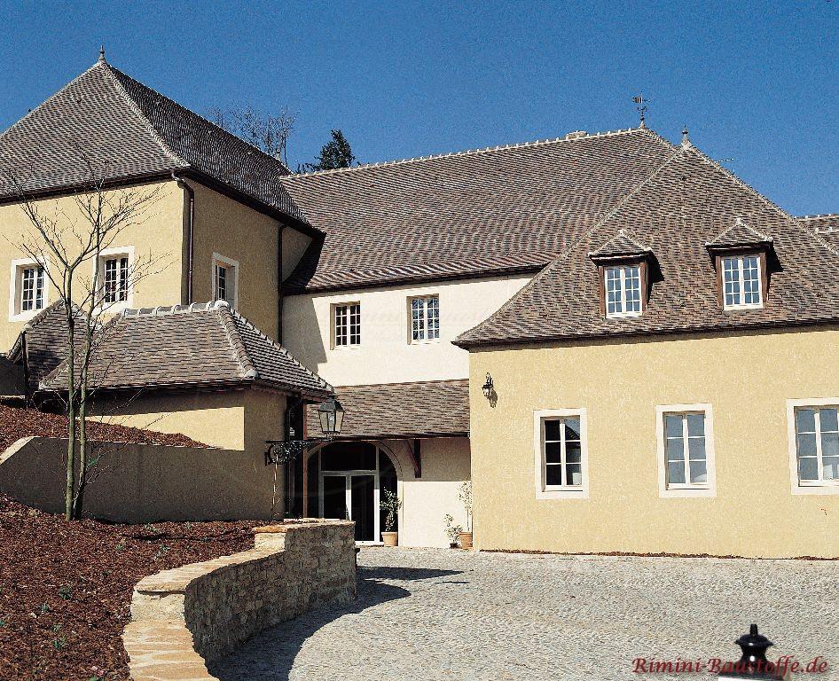 Sehr antik wirkendes Anwesen mit geputzter Fassade und grauen Dachschindeln