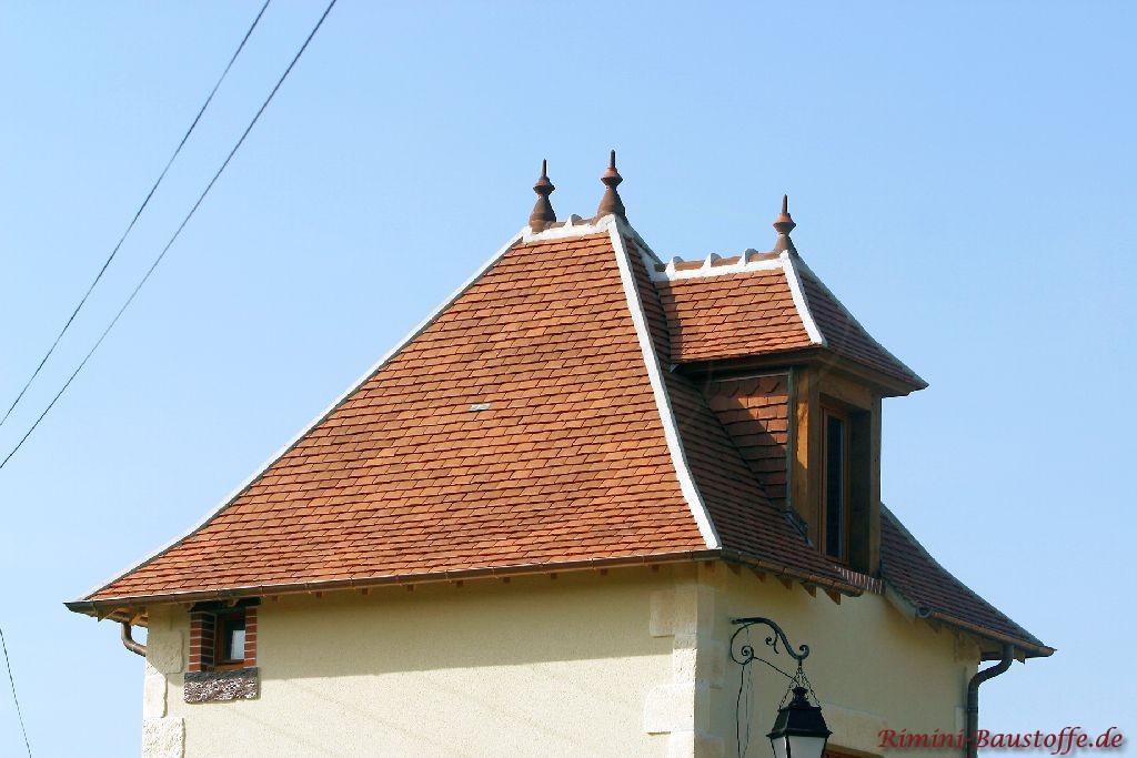 Historischer Kirchturm mit farbigen Tonschindeln und hellen Graten. Auch eine Gaube und Dachschmuck ist zu sehen