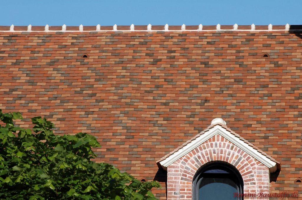 Mehrfarbiges Dach bei einem alten Satteldach. Es wurden hier französische Tonschindeln verwendet. Zu sehem ist auch eine kleine Gaube
