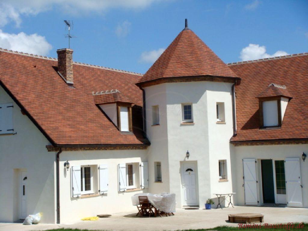 Grosses Einfamilienhaus in Frankreich. In der Mitte ist ein Turm mit Runddach zu sehen, der mit farbigen Schindeln aus Ton abgedeckt ist