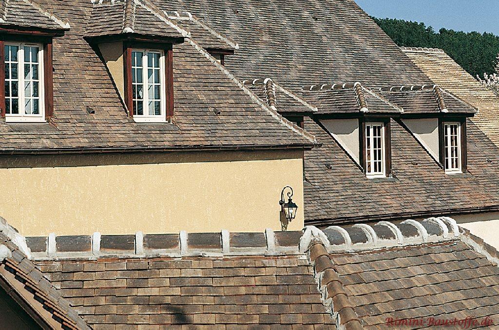 Dachlandschaft mit Tonschindeln in schieferfarben eingedeckt. Diverse Minigauben sind ebenfalls zu sehen