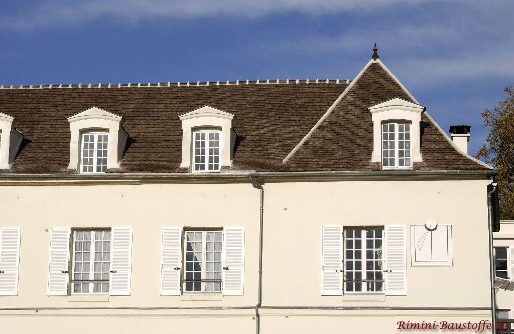 Französisches Schloss mit heller Fassade und weißen Fensterläden. Bei der Dacheindeckung wurden Tonplatten verwendet