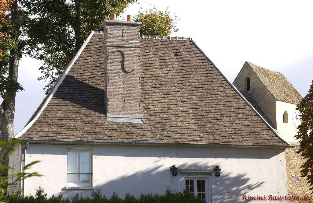 Stark geneigtes historisches Walmdach mit schönem Kamin und Tonschindeln in schieferfarbe