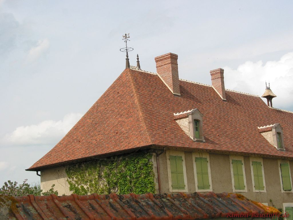 Aufnahme eine Denkmalgeschützem Gebäudes dass mit Dachziegeln in verschiedenen Farben eindeckt wurde. Auch grüne Fensterläden sind
