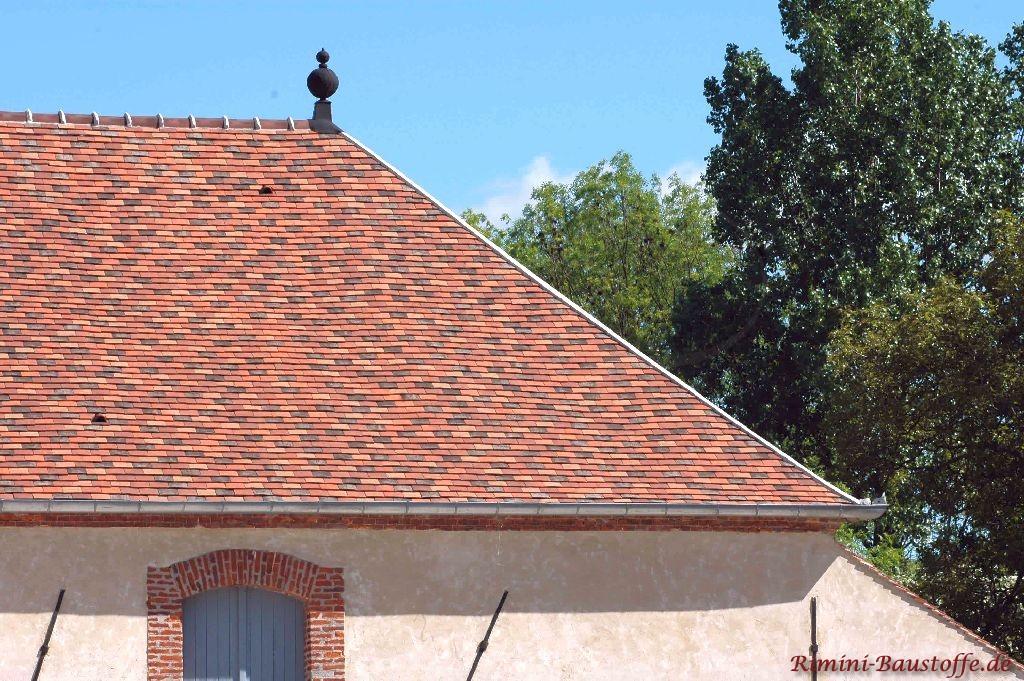 Historisches Gebäude mit rustikalen Dachschindeln in bunten Farben. Auch Dachschmuck ist zu sehen