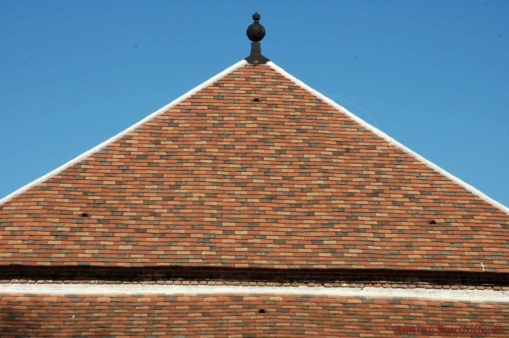 Spitzdach eines Kirchturms mit Ziegelplatten und einer Spitze