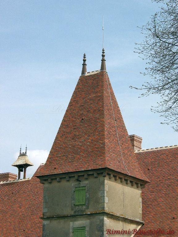Extrem Spitzes Walmdach einer Kirche mit Verzierung. Das Dach wurde mit Tonplatten ausgerüstet