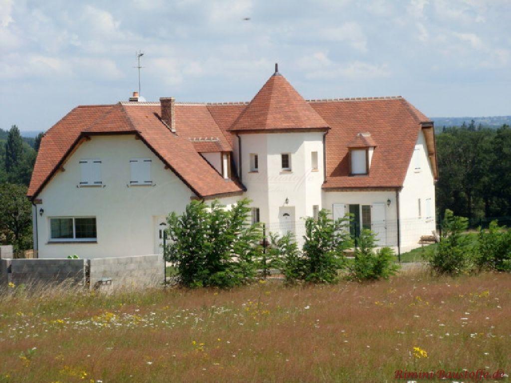 Schönes Zweifamilienhaus mit Rundturm. Es hat eine weiße Fassade und ein rotes Schindeldach