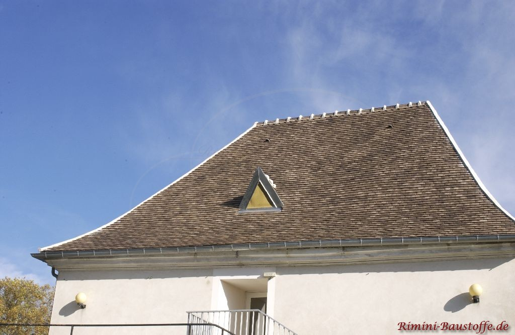 Asymetrisches Schindeldach eines historischen Gebäudes. Die Farben des Daches sind in einem Grauton gehalten. Eine kleine Spitzgaube ist auch zu