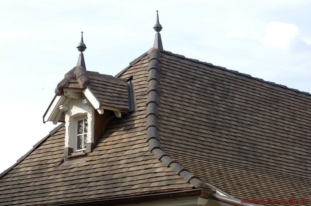 Reich Verzierter Giebel der mit Schindeln in grau ausgeführt worden sit. Zudem ist auch ein Krüppelwalm und auch Dachschmuck zu sehen