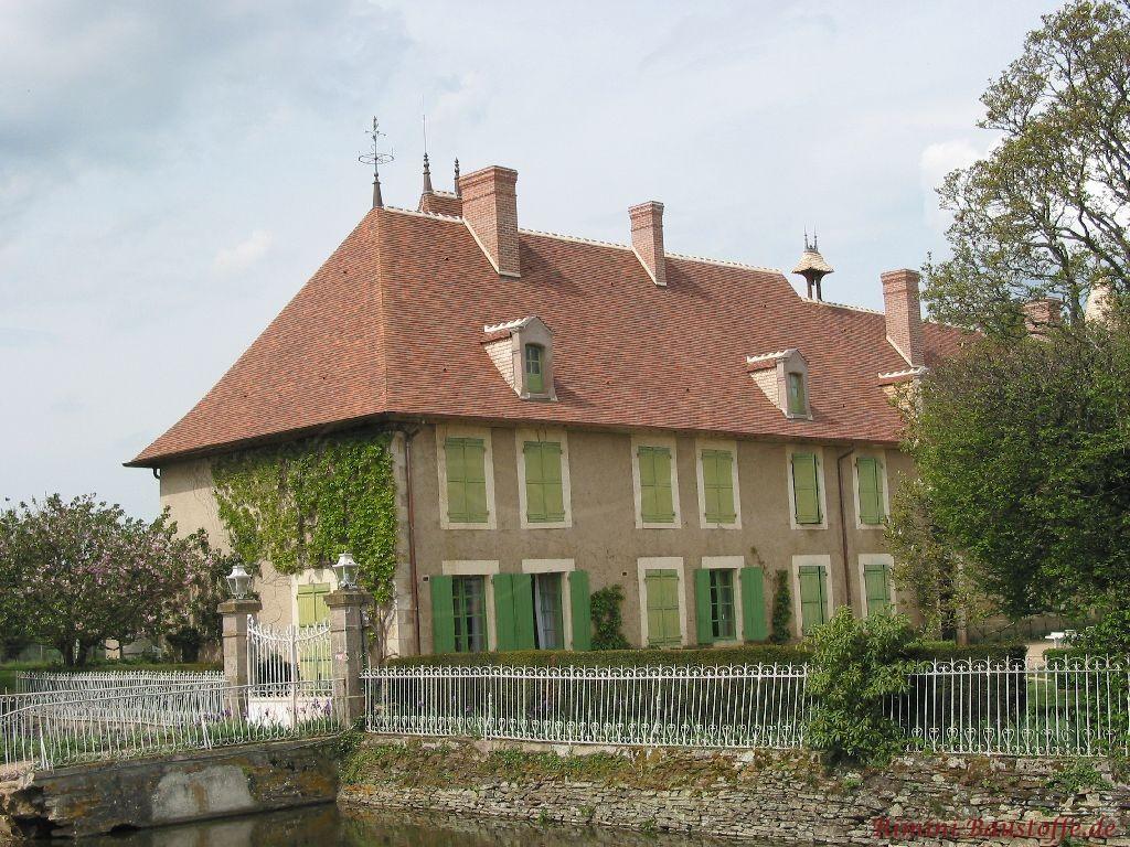 Denkmalgeschütztes Bauernhaus mit grünen Fensterläden und Ornamentfaschen das frisch mit Tonschindeln saniert worden ist