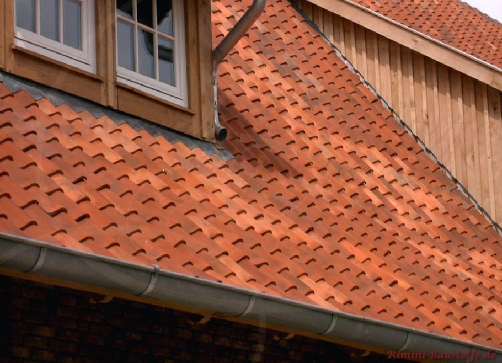 rote changierende Dachfläche mit hölzernen Gauben