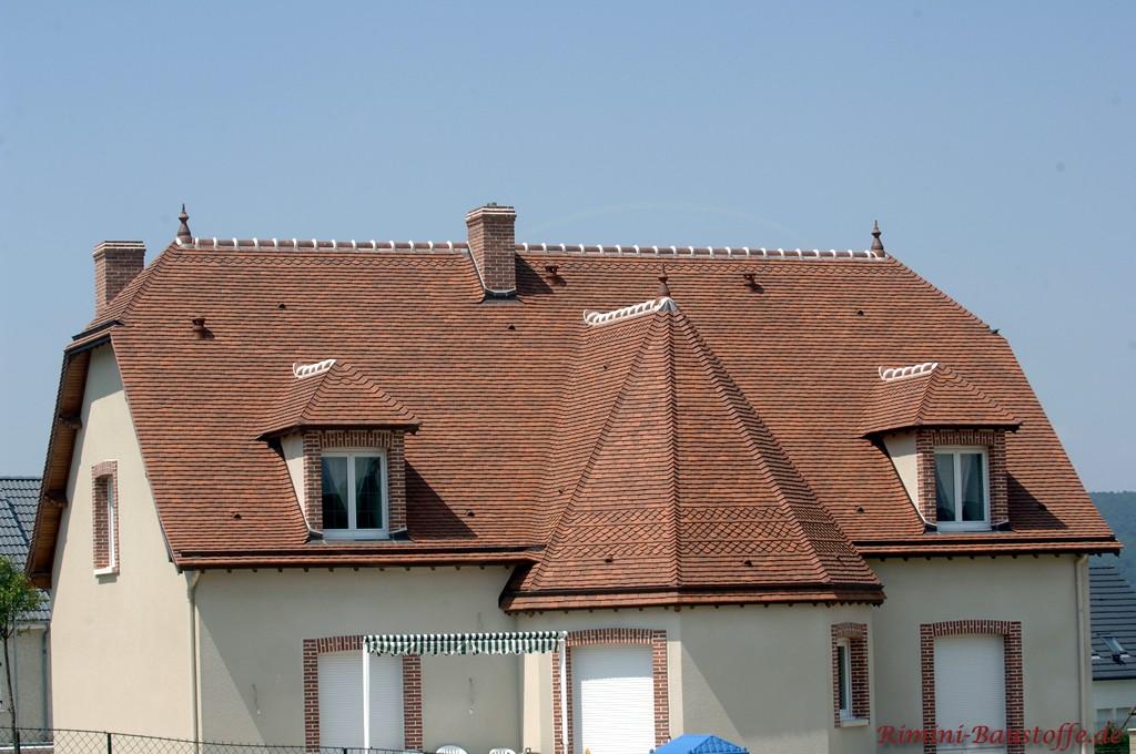 Kleines Einfamilienhaus mit Runddach und zwei Gauben die beide mit Tonschindeln abgedeckt sind