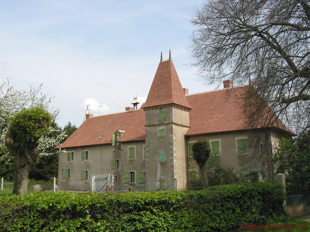 Altes Schloss im saniertem Zustand mit Turm. Die Fenster sind mit hellgrünen Fensterläden ausgestattet. Das Dach wurde mit Tonschindeln rest